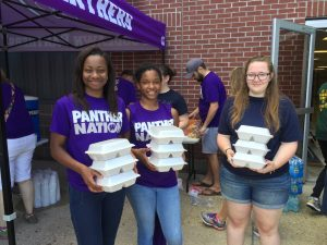 Morgan Watkins and Johnasia Smith help distribute food.